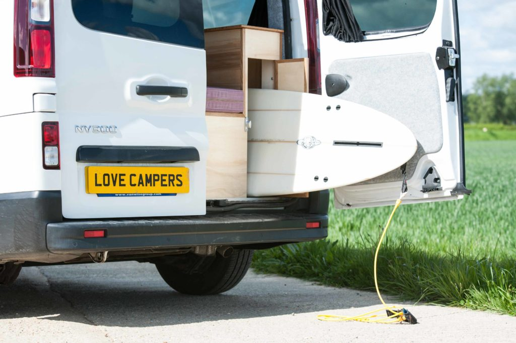 A camper designed for surfing, image features a NV300 Nissan with a surfboard being stowed in the rear.