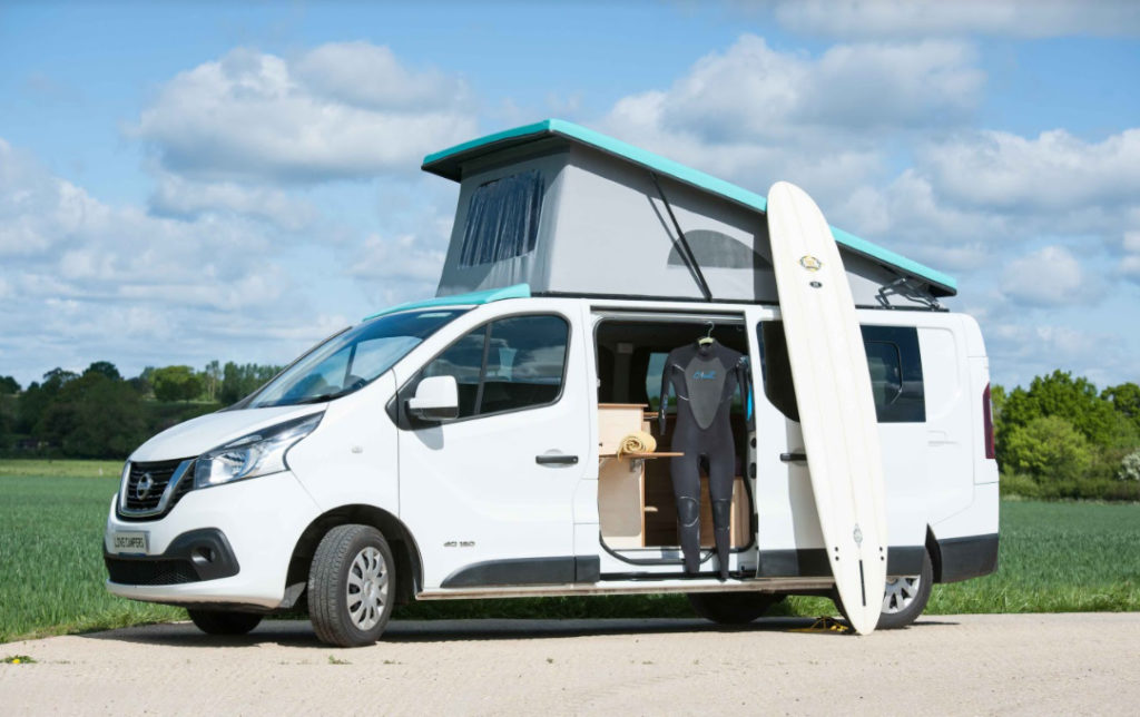 A NV300 with a pop top roof open, the side door open and a surfboard and wet suit on display with the van.